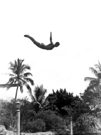 1940s-man-poised-midair-arms-out-jumping-from-diving-board-into-pool
