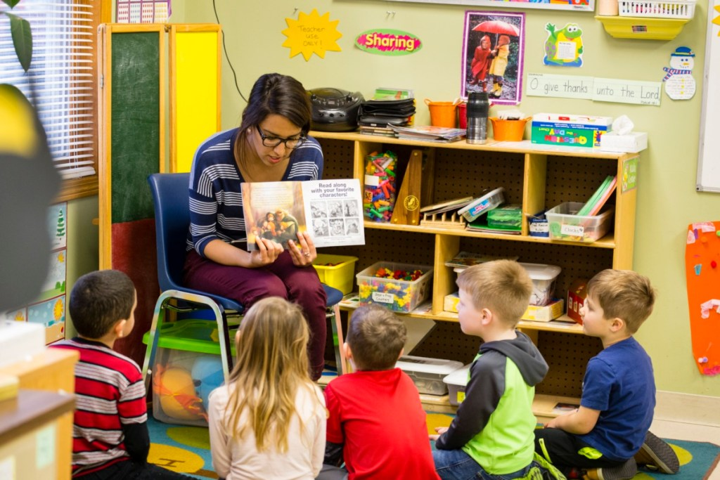girl reads to group of students