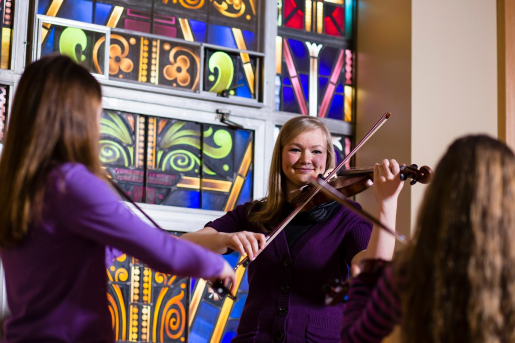 student group teaches two pupils violin in music pedagogy