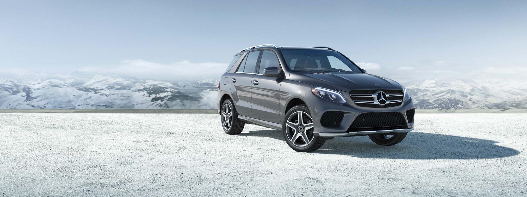 hight resolution of a grey 2019 gle 400 suv parked in front of snow covered mountains