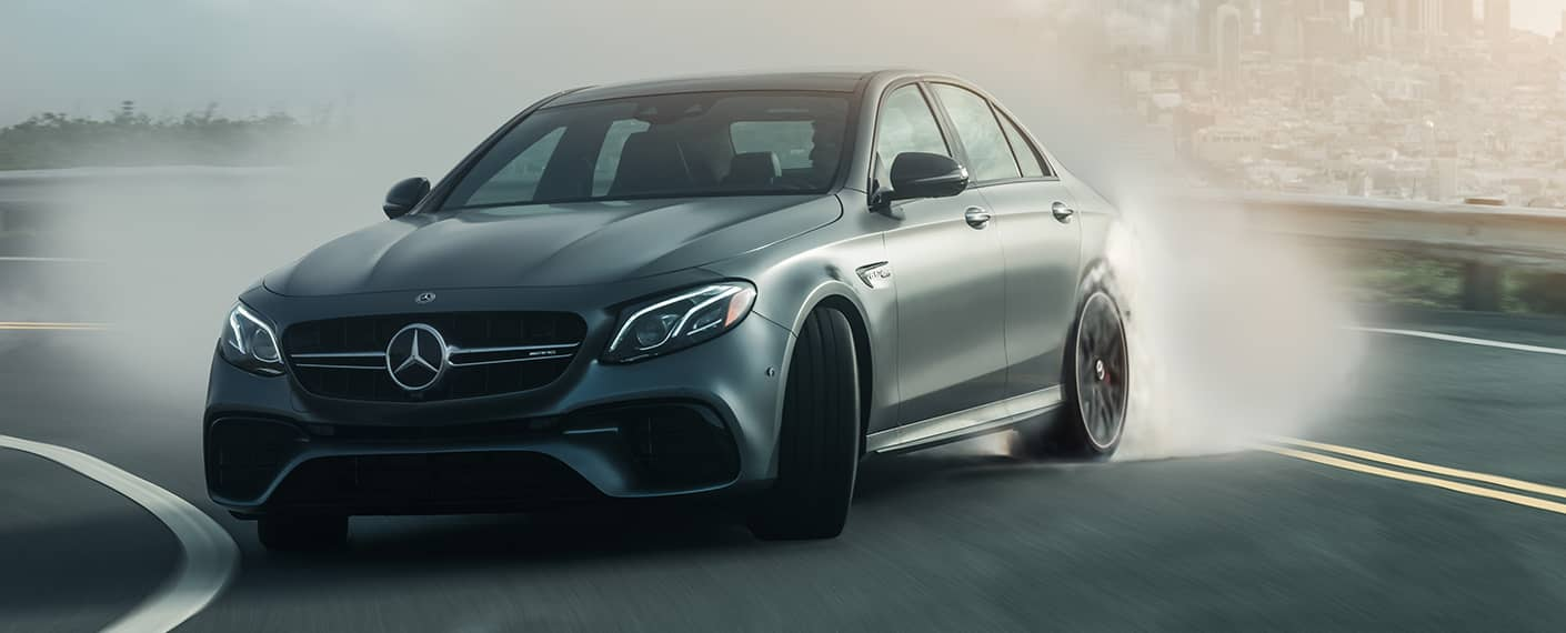 hight resolution of a matte gray mercedes amg vehicle takes a sharp turn at speed