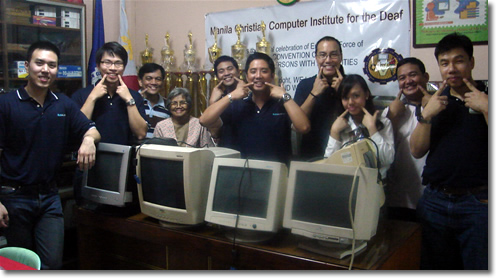 Manila Jaycees give wacky poses behind the second-hand computer monitors they donated to MCCID College.