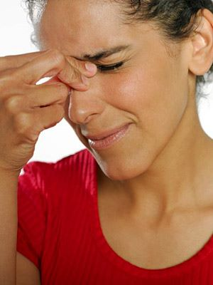 a photo of a woman with sinus pain, aggravated by allergens in her home