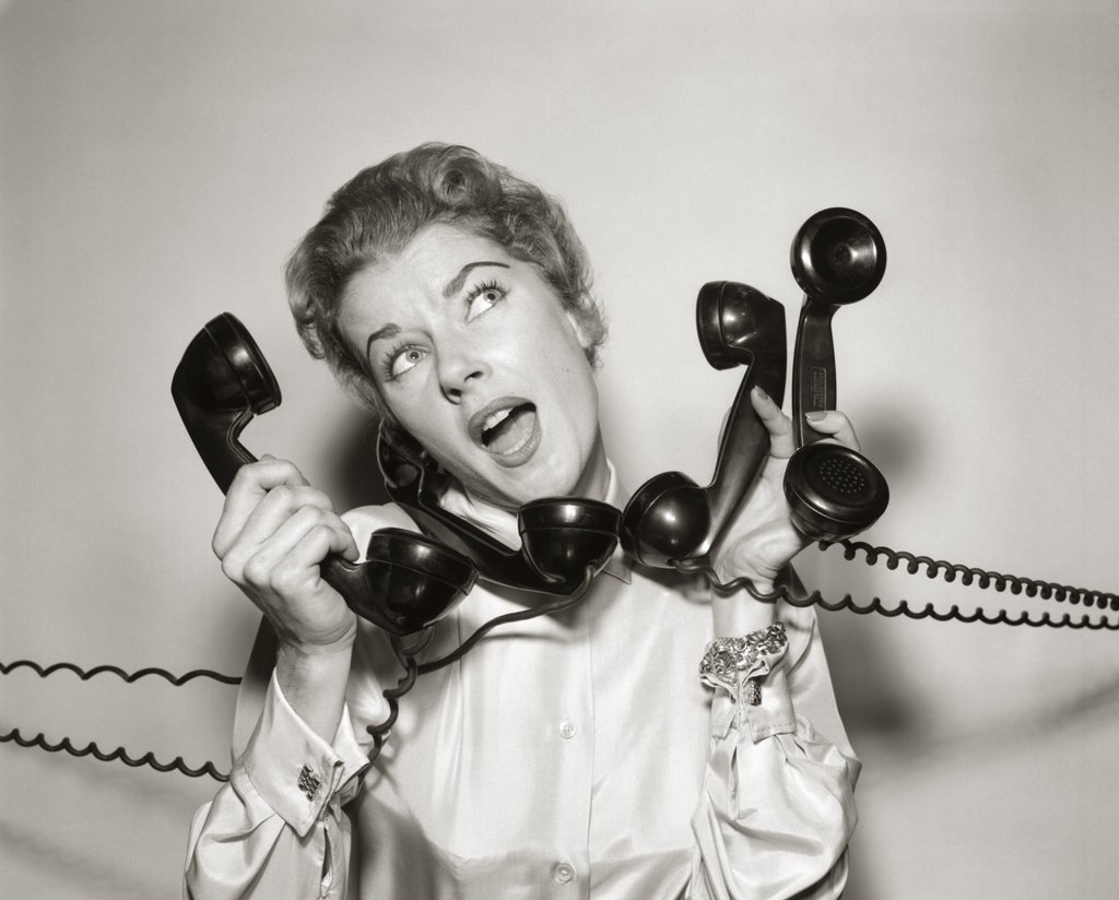 A photo of a woman answering multiple phones at once. It can get that hectic here. Sometimes we're scheduled out three months in advance. Book your fireplace service in the spring to avoid the rush. Schedule for when is convenient for you.