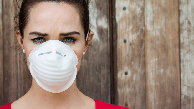 Picture of a woman wearing a face mask to cope with fireplace odors and reduced air quality. Prolonged exposure to fireplace soot smells reduces air quality and health. Get your fireplace service done in the spring to reduce your total exposure time.