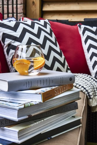 The Outdoor Living Room is a lusciously comfortable space to relax, read and enjoy a beautiful summer afternoon within the black, white and red Pillows and woven throw blankets