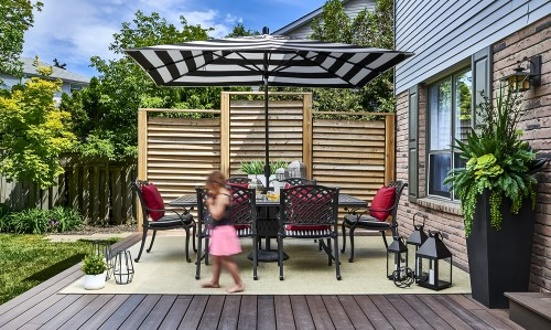 Our Tiny Client enjoying Dynamic Dining on this large composite Deck with cast iron classic furnishings and graphic Dining zone