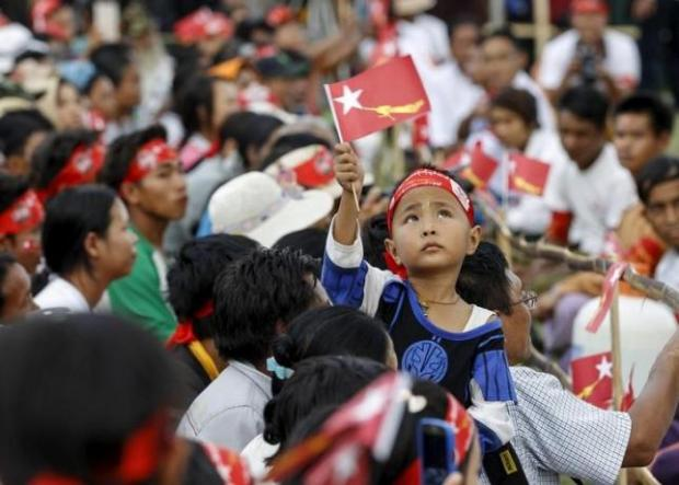 A boy waves the National League for Democracy (NLD) party's flag during Myanmar opposition leader Aung San Suu Kyi's speech as she campaigns for the upcoming general election, in Loikaw capital city of Kayah state September 11, 2015. REUTERS/Soe Zeya Tun