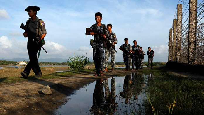 """In this Friday, Oct. 14, 2016 photo, Myanmar police officers patrol along the border fence between Myanmar and Bangladesh in Maungdaw, Rakhine State, Myanmar. Just five months after her party took power, Myanmar's Nobel Peace Prize-winning leader, Aung San Suu Kyi, is facing international pressure over recent reports that soldiers have been killing, raping and burning homes of the country's long-persecuted Rohingya Muslims. The U.S. State Department joined activist and aid groups in raising concerns about new reports of rape and murder, while satellite imagery released Monday, Oct. 31, by Human Rights Watch shows that at least three villages in the western state of Rakhine have been burned. Myanmar government officials deny the reports of attacks, and presidential spokesman Zaw Htay said Monday that United Nations representatives should visit """"and see the actual situation in that region."""" (AP Photo/Thein Zaw)"""