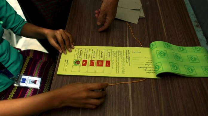 An European Union personnel serving as an election overseer in Myanmar's upcoming general elections demonstrates how to fill up a ballot paper in Yangon, Myanmar October 30, 2015. REUTERS/Soe Zeya Tun