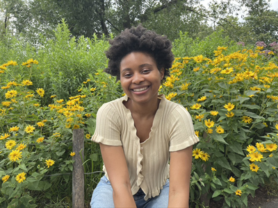 Kadi Ba is sitting and smiling in front of a shrub of yellow flowers. She is wearing a light tan short-sleeved cardigan and light blue jeans.