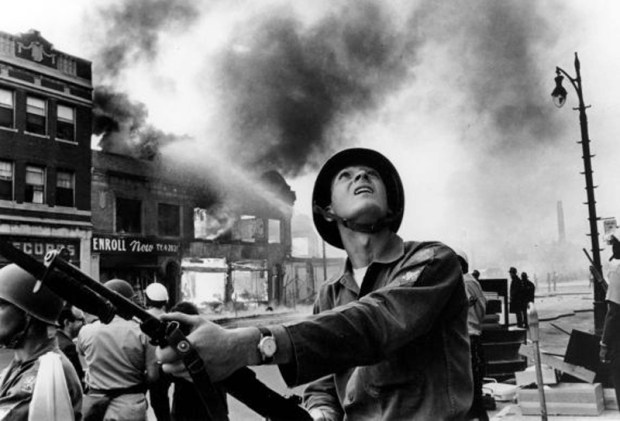 A National Guardsman on foot looking for snipers on rooftops as firemen battle blaze. Detroit, July 25, 1967