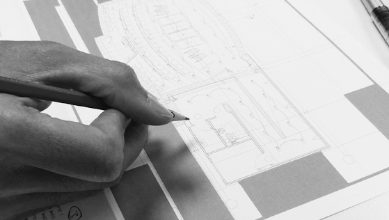 Person holds pencil and details blueprints for smart home