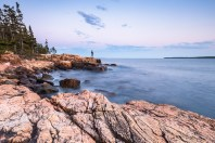 A person stands on the rocky shore, looking out over the ocean in Acadia National Park, Mount Desert Island, Maine.
