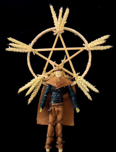 Small Lughnasadh corn dolly with a brown cape and antlers made of corn husks, with a woven pentagram made of wheat behind it