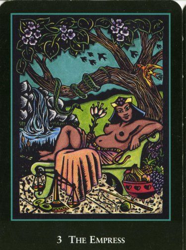 The Empress, World Spirit Tarot. A dark-skinned femme lounges in a relaxed position on a couch. She holds a lotus blossom, She is surrounded by fruits, veggies, and other symbols of abundance. A serpent winds around a branch in the tree above her.