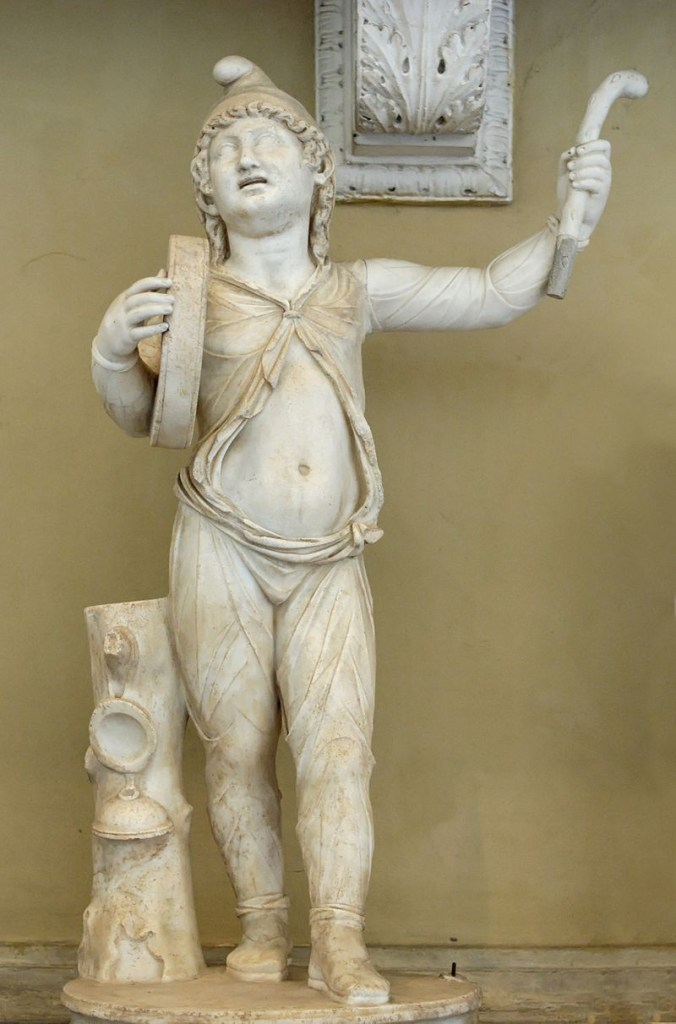 Megalesia. A white marble sculpture of a Roman Imperial Attis wearing a Phrygian cap and performing a cult dance. They hold a drum or tambourine and priapic wand.
