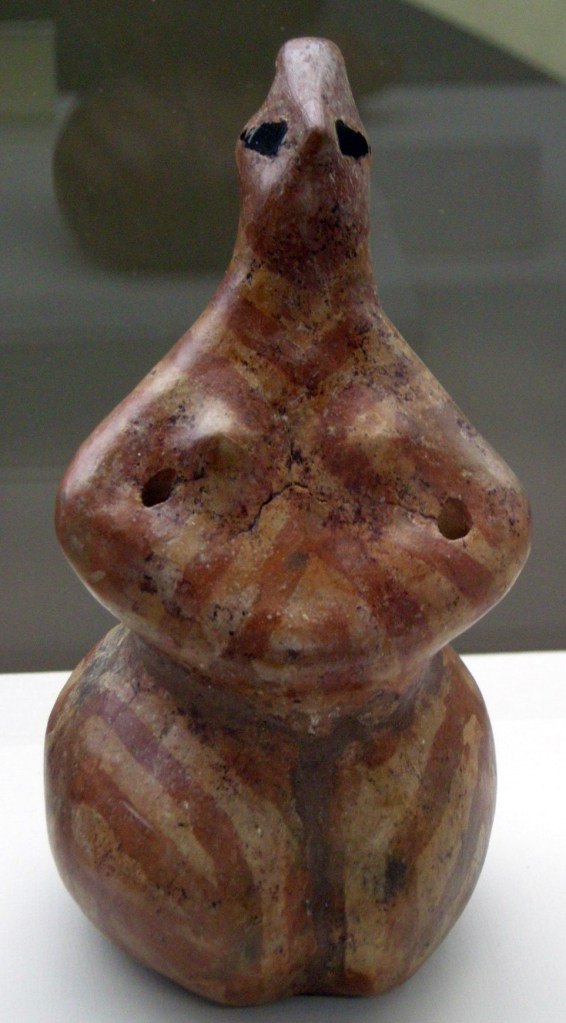 Megalesia. Statuette from Hacilar (5250-5000 BC). A red and white striped figure with black eyes, holding their arms in front of their torso.