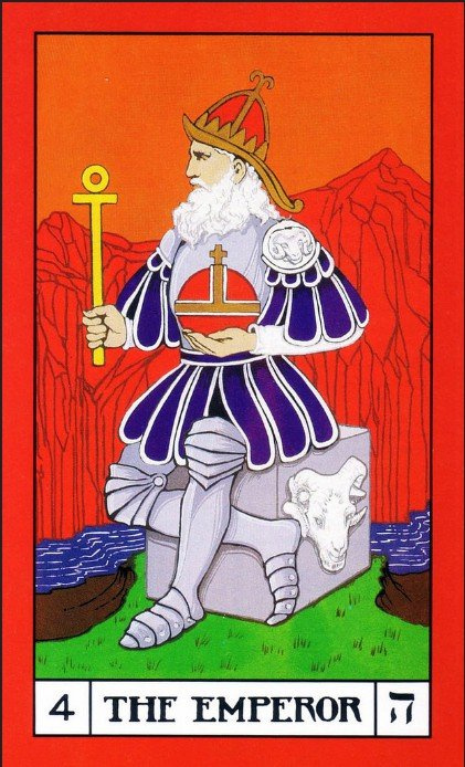 The Emperor Card, Builders of the Adytum Tarot. A light skinned, older, masculine person with a white beard sits on a gray stone cube. There is a ram's head on the side. They are on grass, near a stream. Red mountains in the background with an orange sky. The person is wearing silver and navy armor. They wear a red and gold helmet. They hold a gold scepter, and a red and gold orb. Their legs are crossed at a 90º angle. They are looking off into the distance, and you can only see half their face.