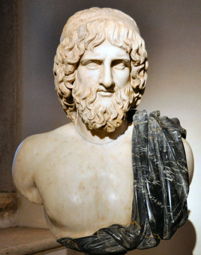 Februus, possibly a deity celebrated during the festival Lupercalia. A white marble sculpture depicting the head, shoulders, and chest of a middle aged thin Greek man with curly hair framing his face and a curly beard and mustache. He has piercing eyes, and a long nose. He has a black marble sash over his shoulder.