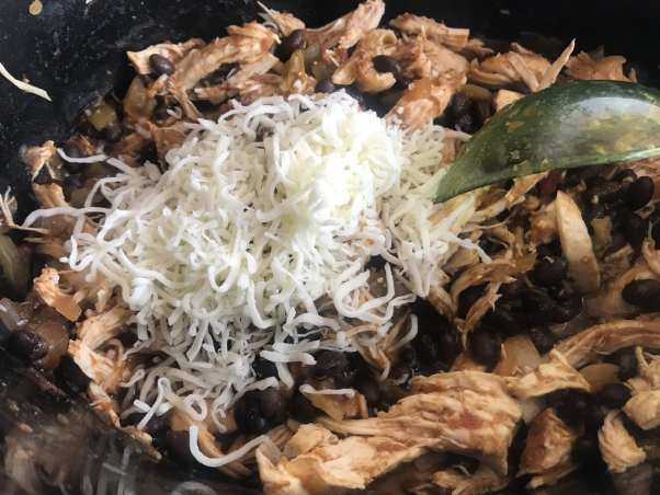 Add black beans and cheese to the shredded Mexican cheese in Chicken Tostadas.