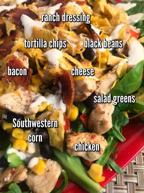 Ingredients to make a delicious Southwest Chicken Bacon and Ranch Salad: salad greens, chicken, bacon, cheese, Southwest corn, black beans, tortilla chips, and Ranch dressing.