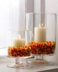 How simple is this? a couple white candles surrounded by candy corn.  You can use any type vase or candle holder