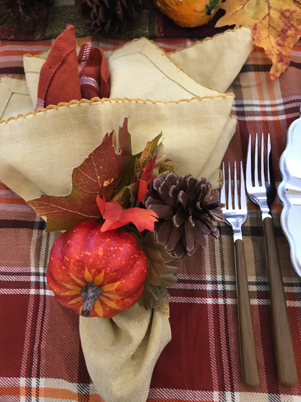 Autumn dining with double napkins fastened with pumpkin napkin ring.