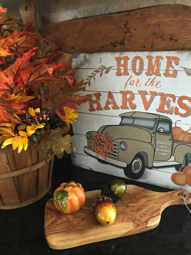 Autumn home for harvest vignette with farm truck full of pumpkins.