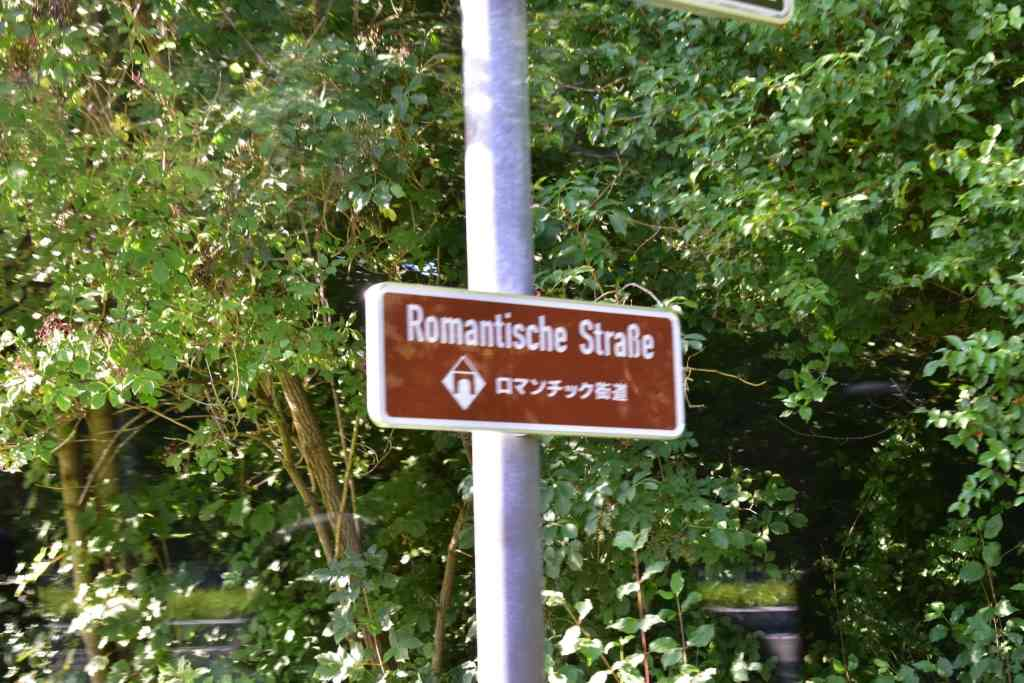 brown road sign indicating the Romantic Road