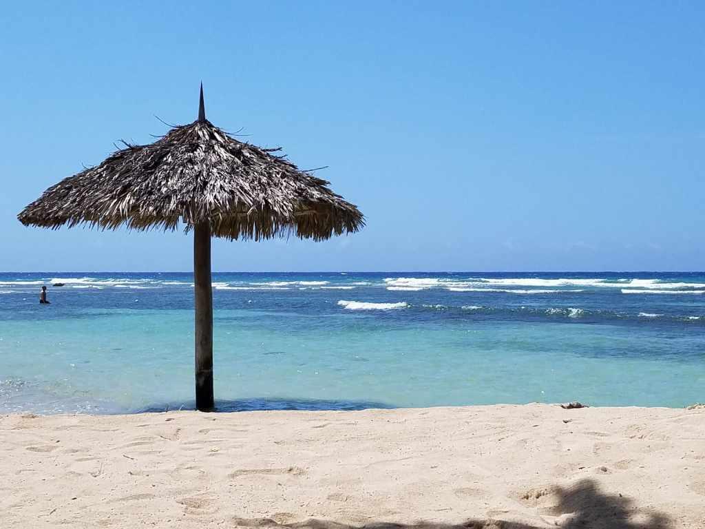 tiki hut umbrella on white sand beach with teal blue water