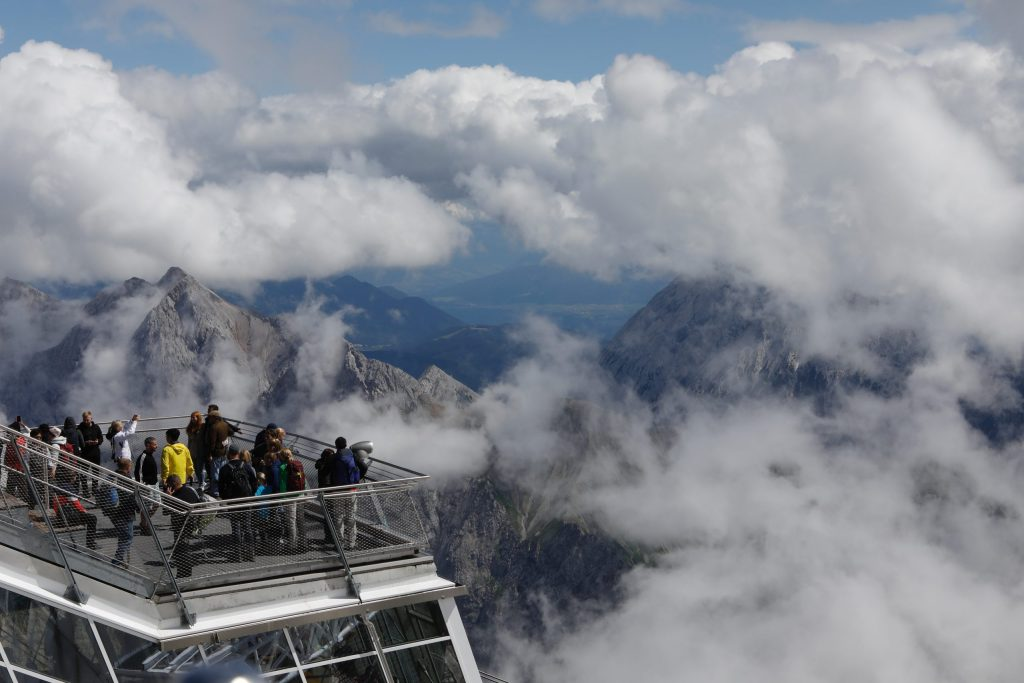 people on viewing platform in clouds and mountains of germany