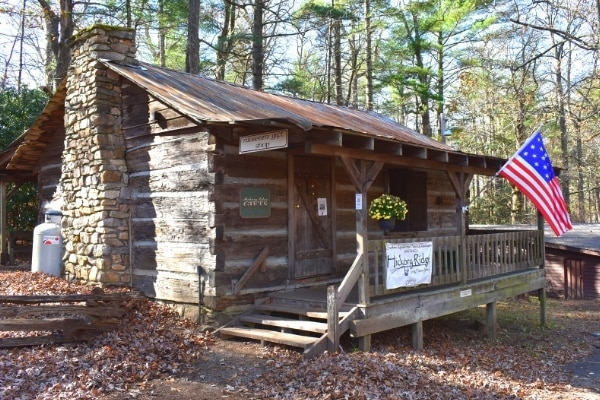 Log cabin visitor center with historic American flag waving at the Hickory Ridge History Museum in Boone, NC