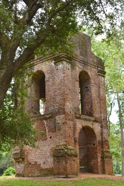brown brick church tower ruins in a green forest