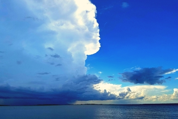 Tall and dark storm clouds soar over the ocean from the right contrasting with the bright blue sky on the left