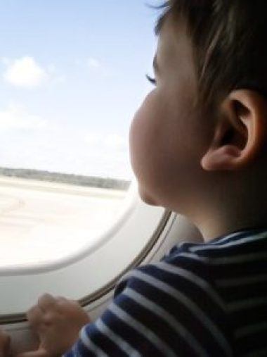 little boy looking out airplane window