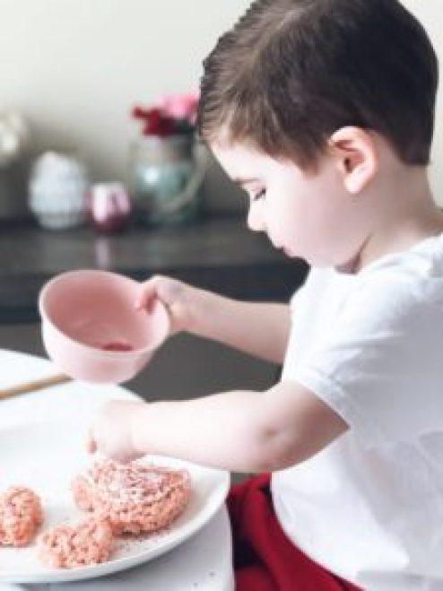 toddler decorating pink valentine heart-shaped rice krispie treat with sugar sprinkles