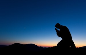 Man praying on the summit of a mountain at sunset.