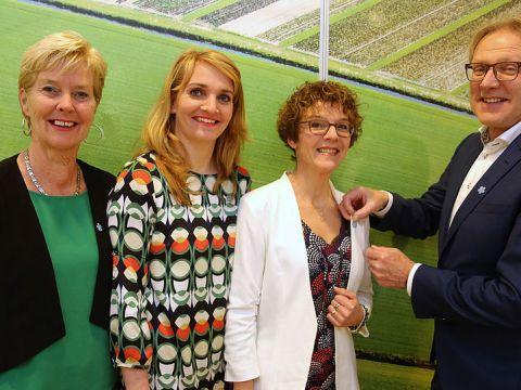 """Raadsleden Claudia Selders, Saskia Schouten en Els van den Bosch ontvingen donderdag 10 januari uit handen van wethouder Dirk Kuipers het speciale""""Vergeet-mij-niet-speldje""""."""