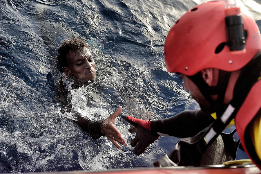 "TOPSHOT - A migrant is rescued from the mediteranean sea by a member of Proactiva Open Arms NGO some 20 nautical miles north of Libya on October 3, 2016. Thousands of migrants are ""racing against the clock"" to make the perilous crossing from Libya to Europe before summer ends, with authorities in the conflict-torn country at a loss to stem the flow. / AFP / ARIS MESSINIS (Photo credit should read ARIS MESSINIS/AFP/Getty Images)"