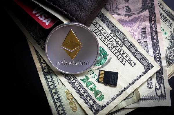 Silver and gold ethereum coin with us paper money.