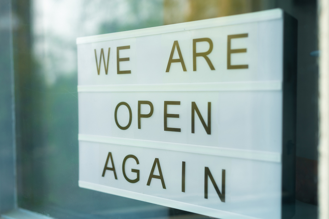 We are open again sign on a store front.