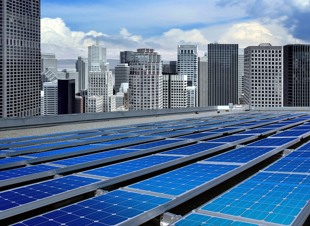 Solar panels in a city with sky scrapers in the background.