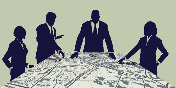 Group of people around a table looking at a large map.