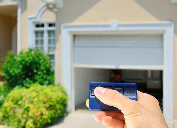 Person using a remote garage door opener.