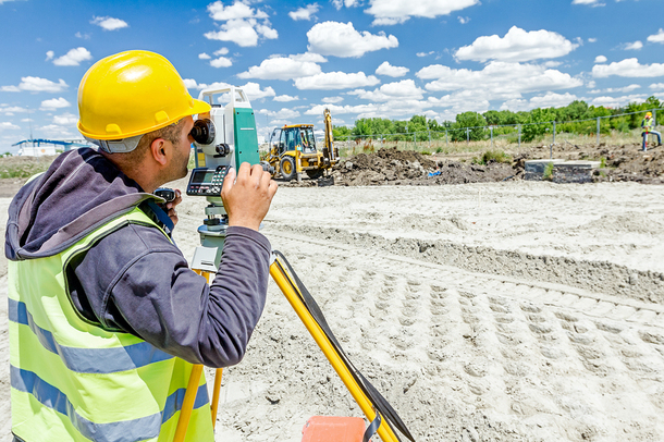 Engineer using surveying equipment at a construction site.