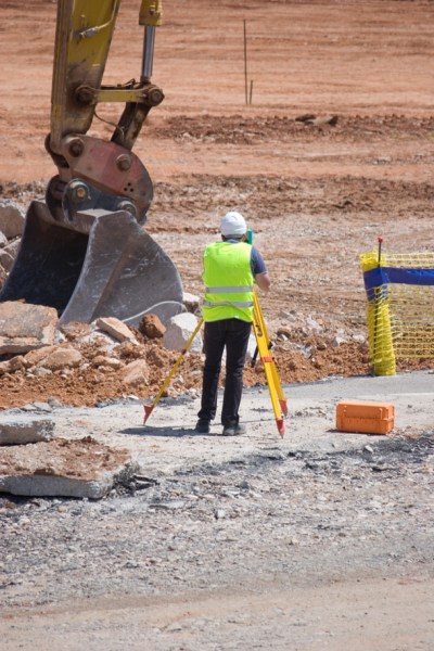 Engineer using surveying equipment at a construction site with a backhoe in the background.