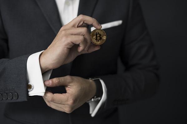 Man holding a golden bitcoin coin.