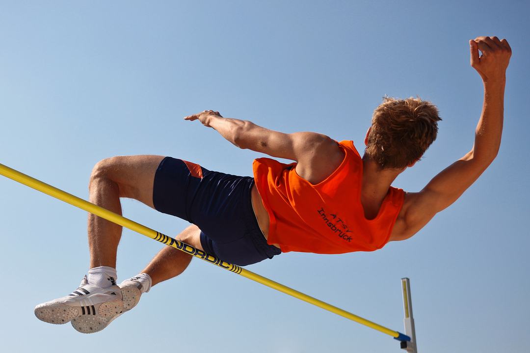 Athlete leaping over a pole.