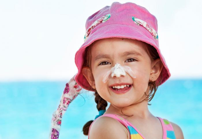 A child wearing sunscreen and a sunhat